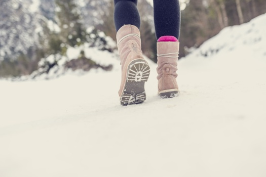 Active woman walking away from the camera through winter snow