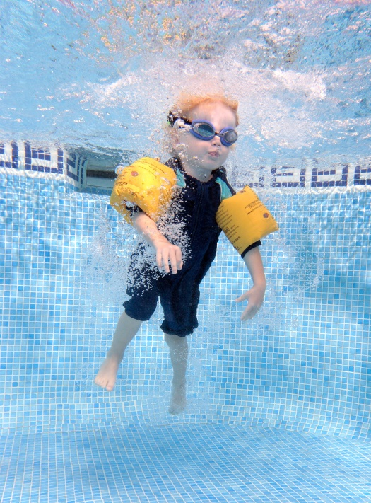 young boy jumping into a swimming pool