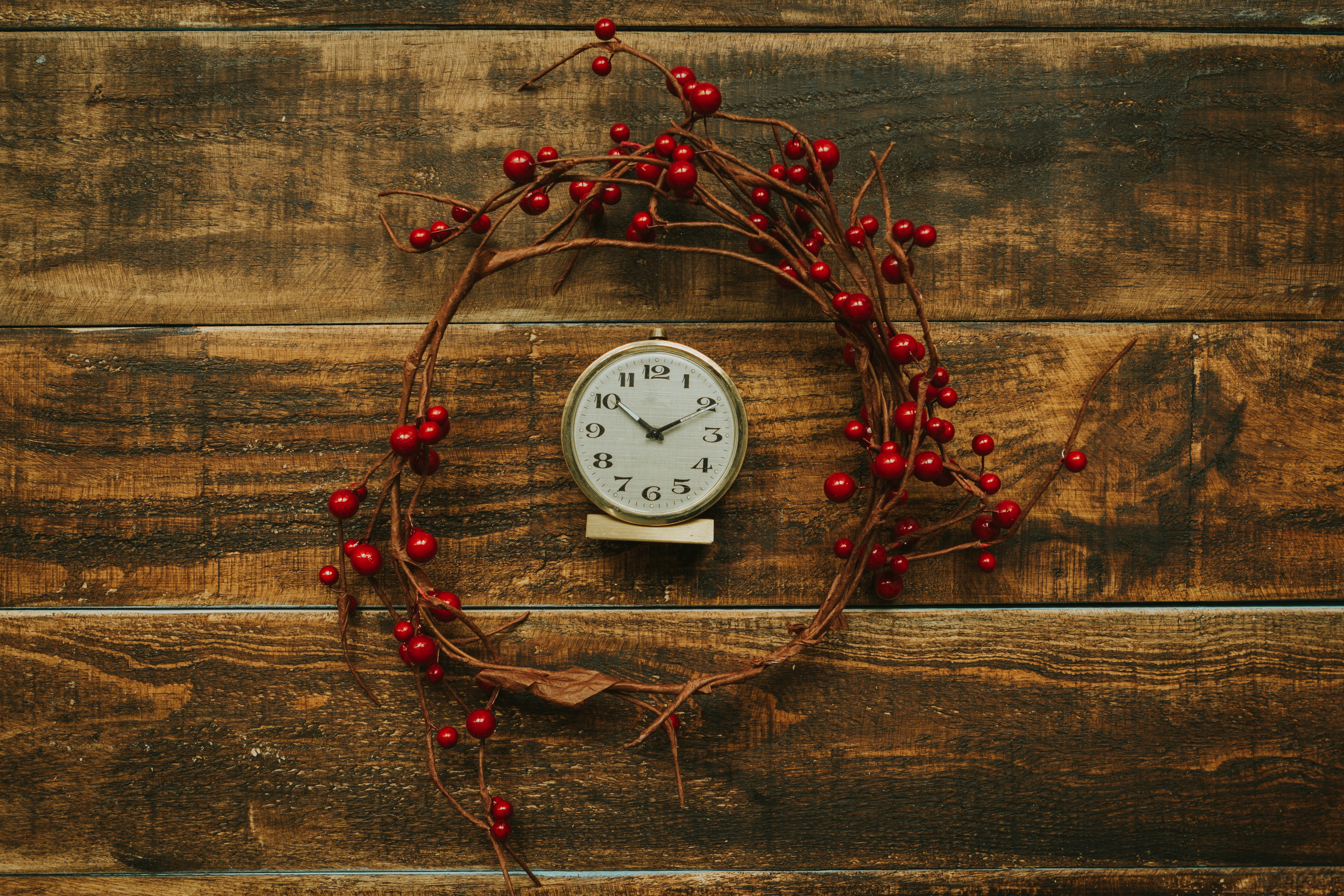 Old golden alarm clock with red berries